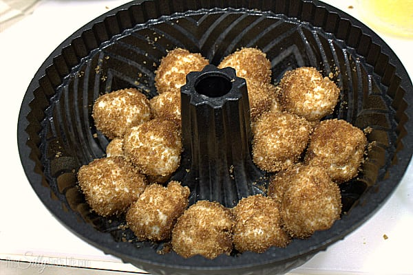 , roll them in the melted butter then into a separate bowl that has the brown sugar and cinnamon combined. Place into a bundt pan that has been sprayed with cooking spray. Repeat this process until all the biscuits are done. Cover with plastic wrap and let sit in fridge over night.