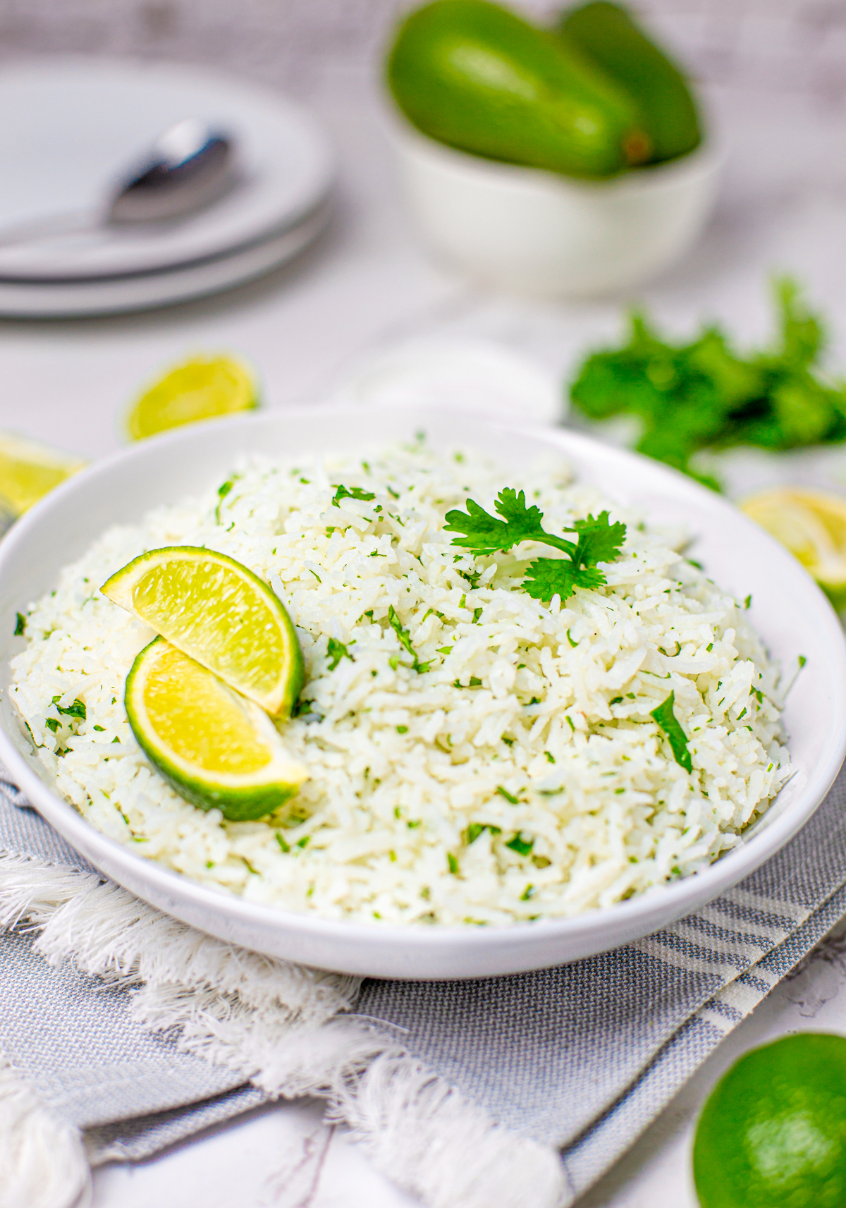 White bowl of Cilantro Lime Rice in bowl with limes and cilantro