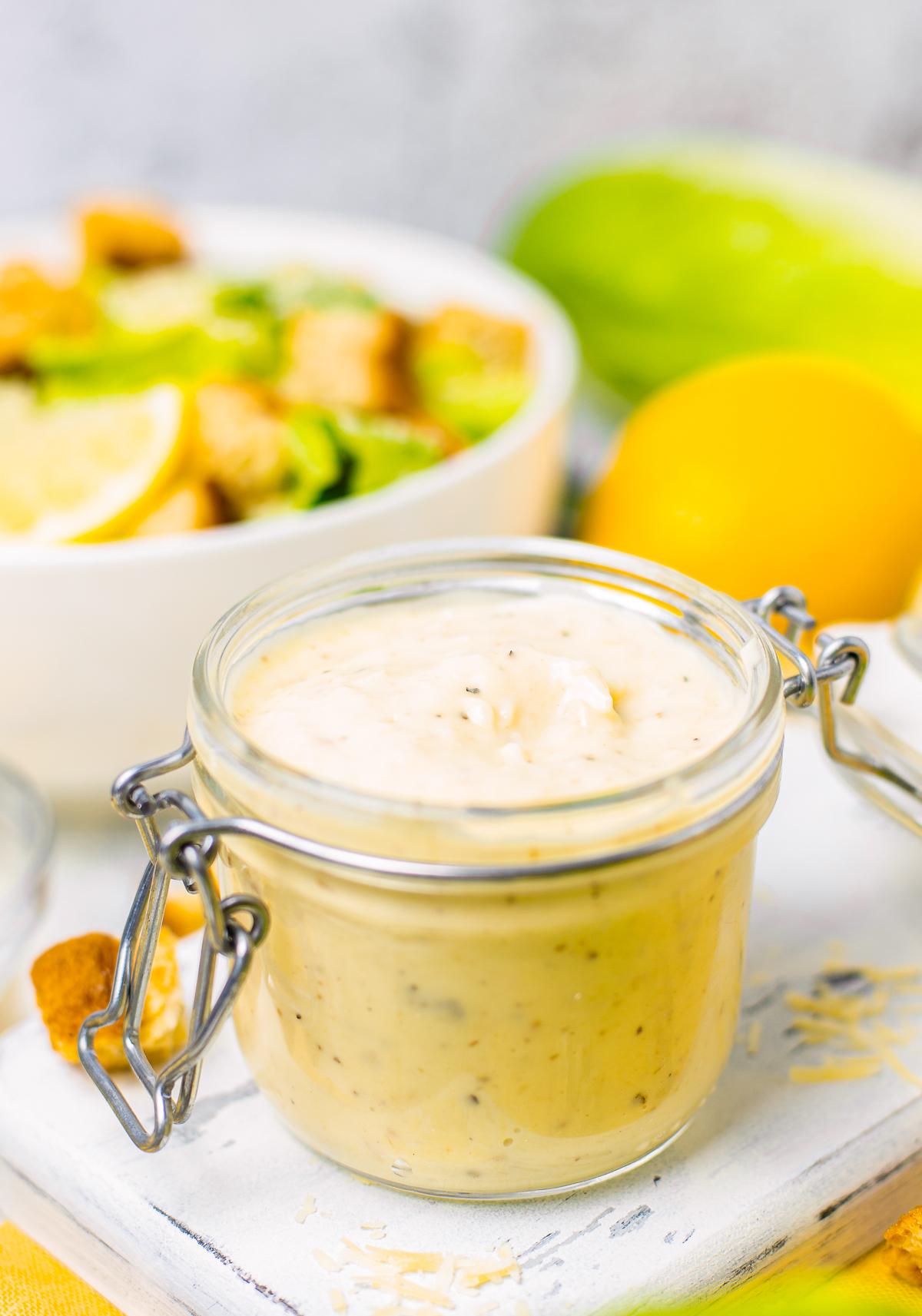 Homemade Caesar Salad Dressing in open jar on white platter.