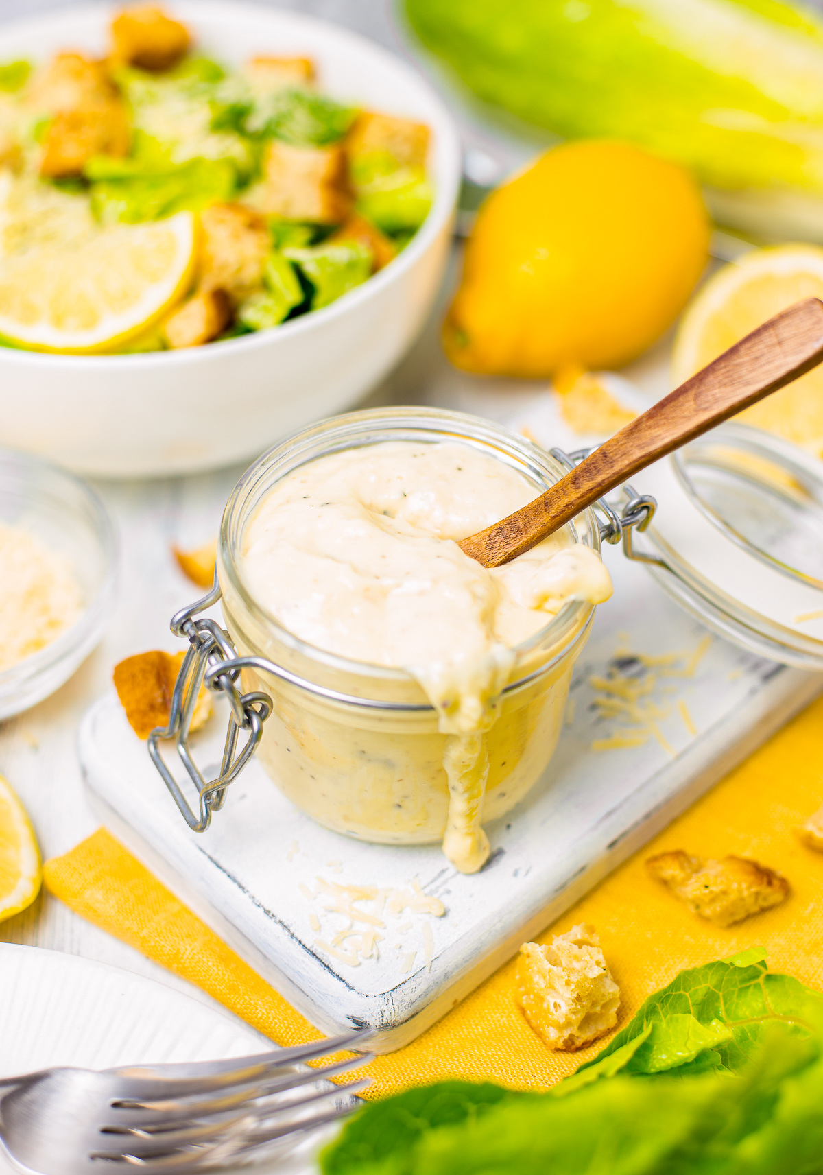 Spoon in Caesar Salad Dressing with it dripping down side of jar.
