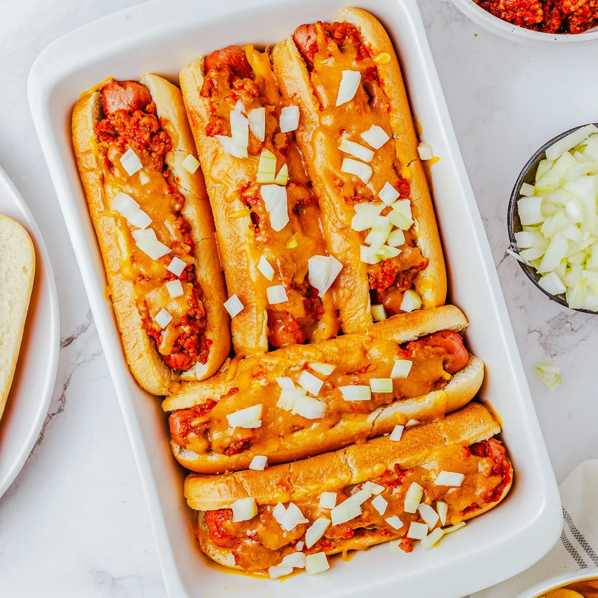 Square overhead image of finished Chili Cheese Dog Recipe topped with onions