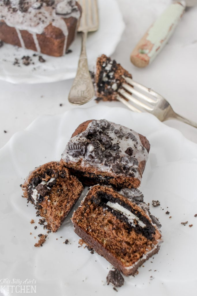 Mini Cookies and Cream Banana Bread Loaves, chocolate banana bread stuffed with chocolate sandwich cookies and topped with cookies and cream glaze! Recipe from ThisSillyGirlsKitchen.com