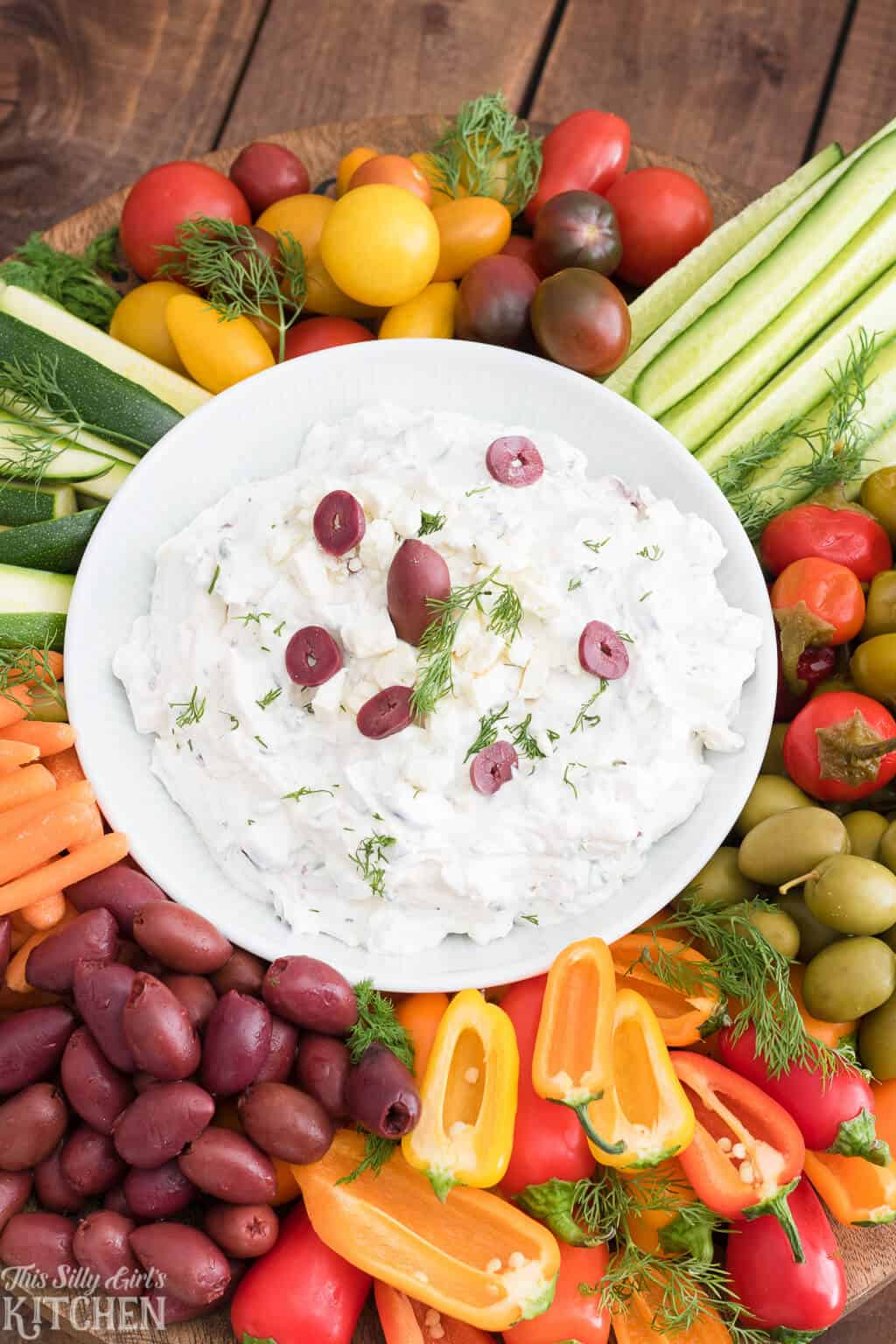 Close up overhead photo of finished dip in white bowl with various vegetables