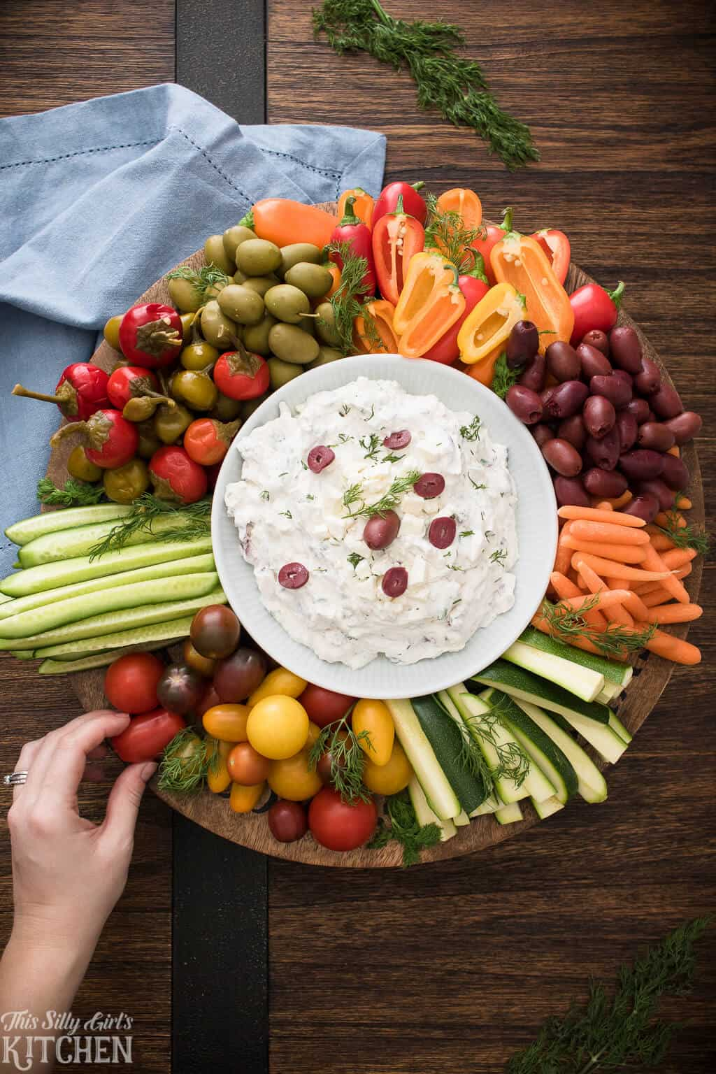 Hand placing vegetables on tray with Greek Yogurt Dip in center overhead photo