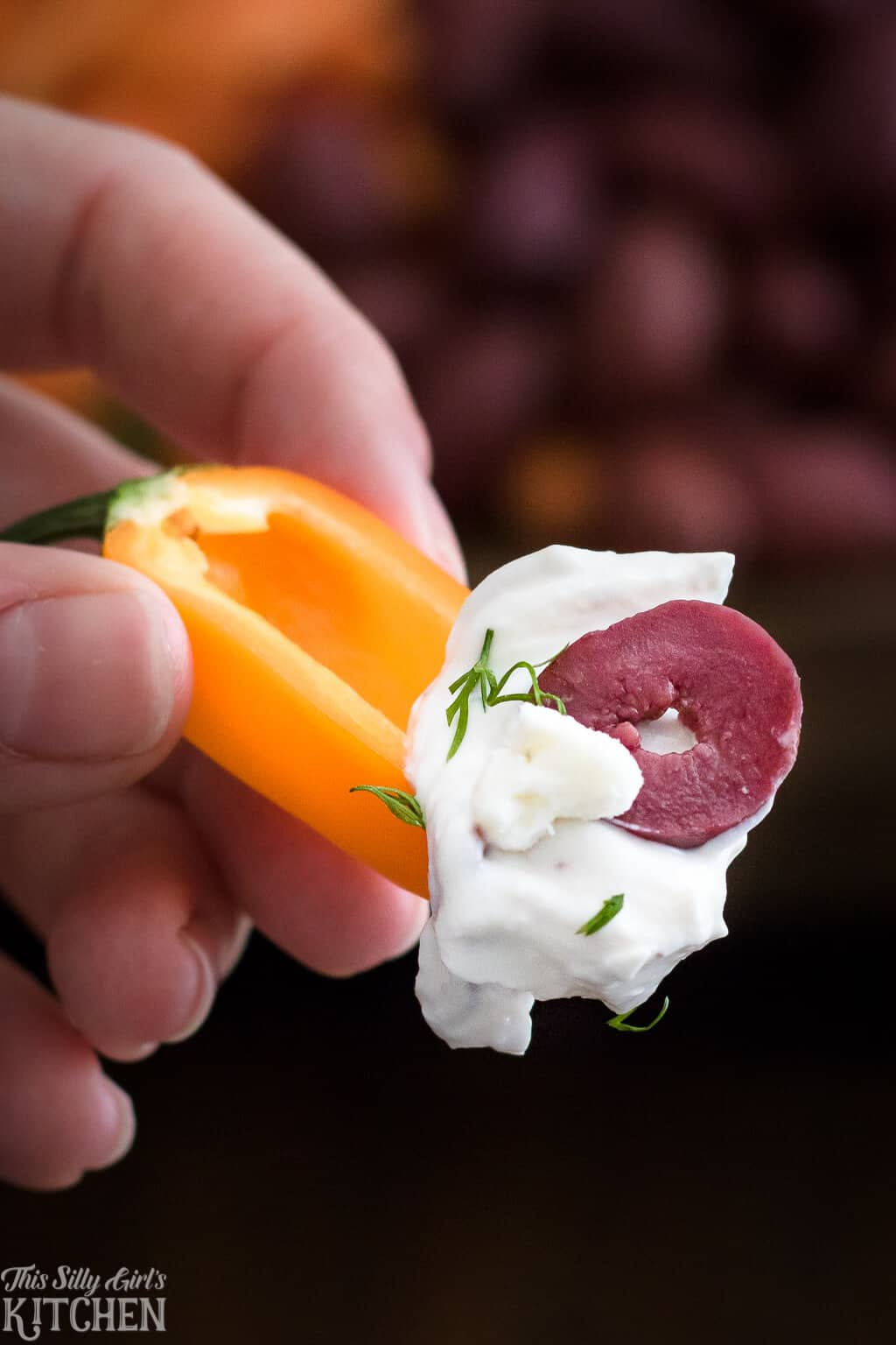 Hand holding a small pepper with some Greek Yogurt Dip on it and slice of olive