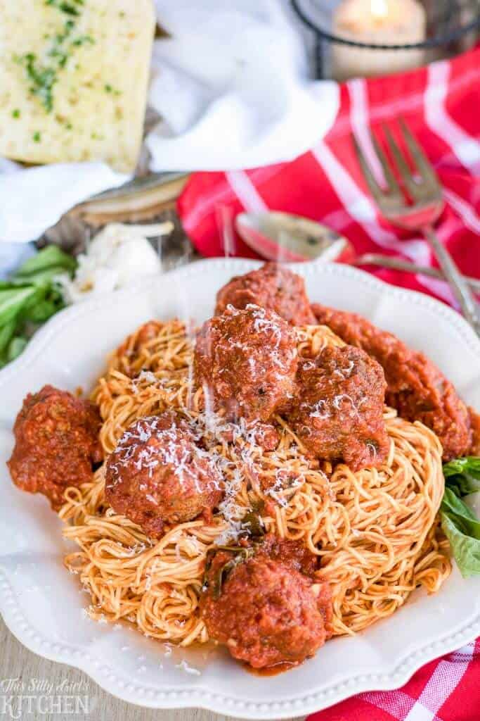 Close up of Sauce and Meatballs over spaghetti on white plate