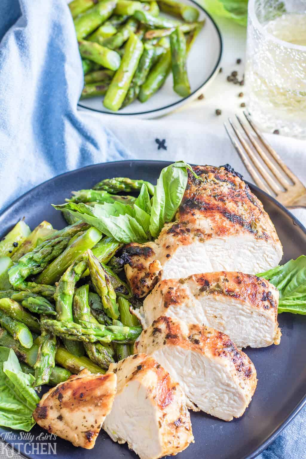 Pesto Chicken Marinade on cut up grilled chicken on plate with asparagus