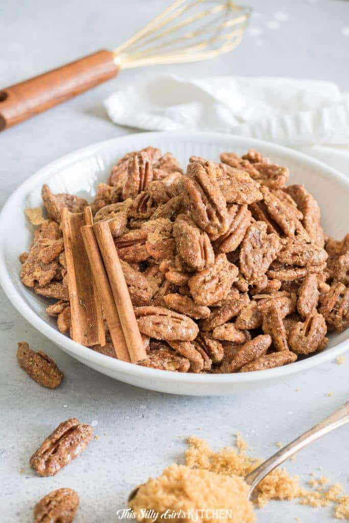 Roasted Pecans in white bowl with cinnamon sticks