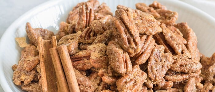 Roasted Pecans in white bowl close up with cinnamon sticks