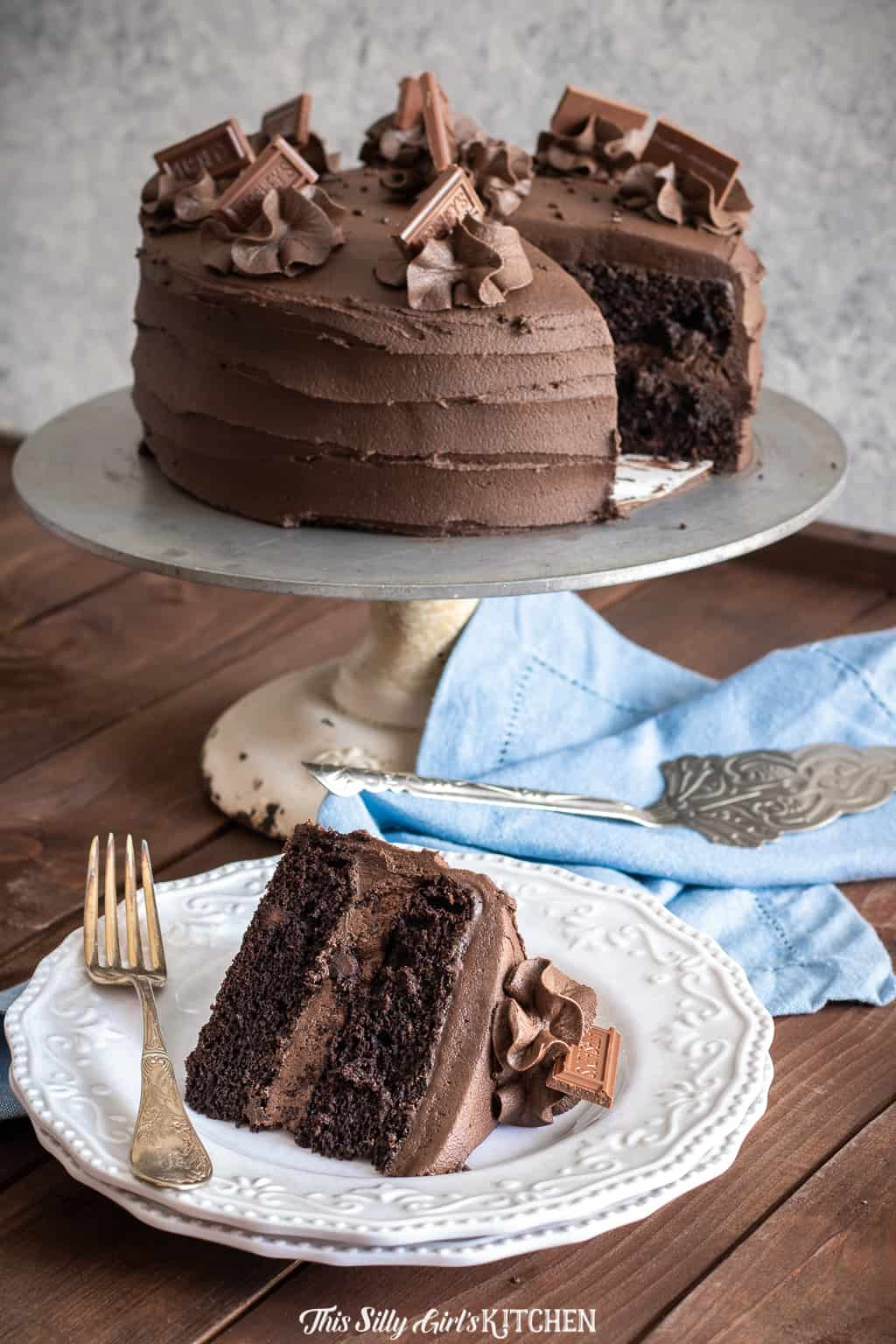 Chocolate Layer Cake on cake stand with slice missing which is on white plate