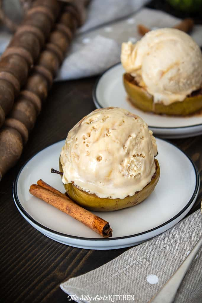 Baked Apples Recipe on plate with ice cream and cinnamon stick.