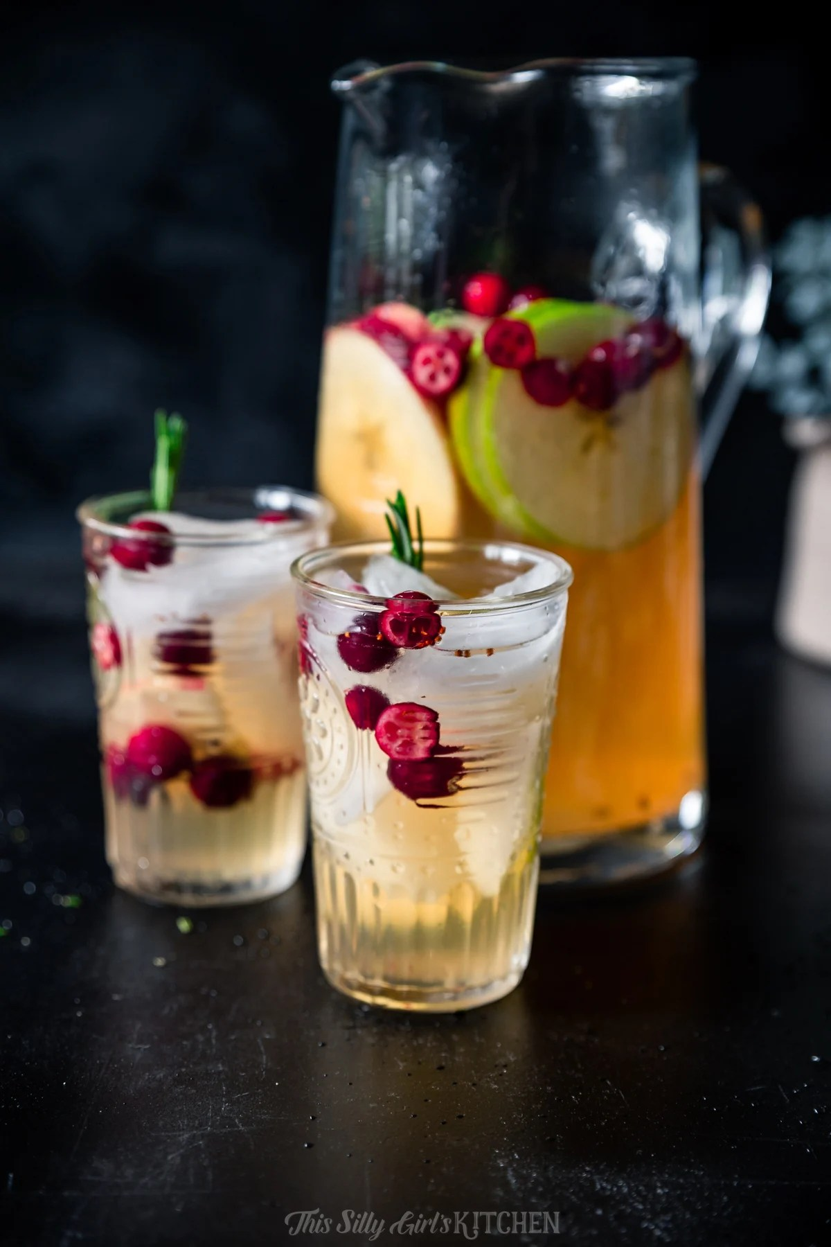 Two glasses and pitcher of white wine sangria on black table