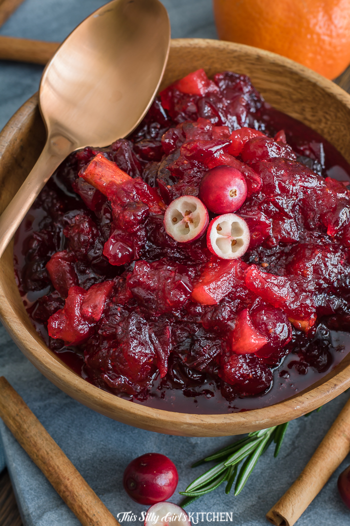 Close up of Cranberry Sauce in bowl with golden spoon and cinnamon sticks