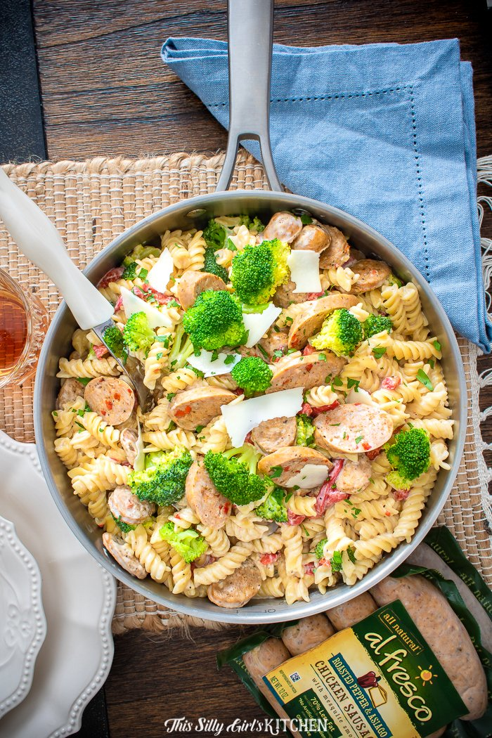 Ready in under 25 minutes, creamy, loaded with broccoli, chicken sausage, and roasted red bell peppers. This chicken broccoli pasta is a knock-out dish! #recipe from thissillygirlskitchen.com #chicken #alfrescochickensausage #broccoli #pasta #onepot #cheese #creamypasta