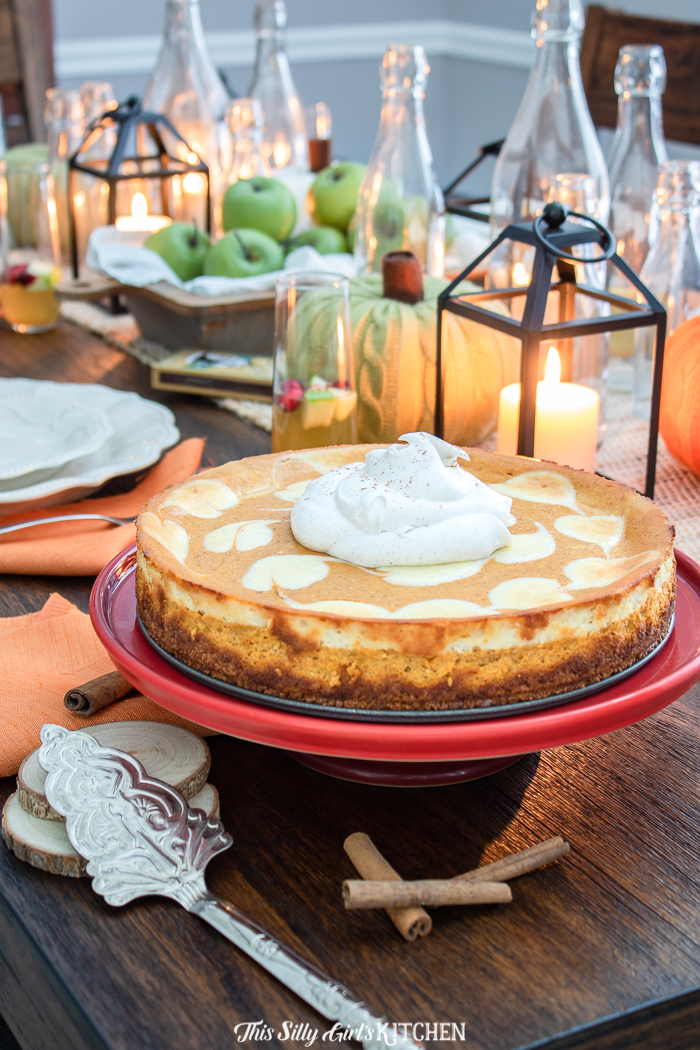 Whole Pumpkin Cheesecake on stand topped with whipped topping