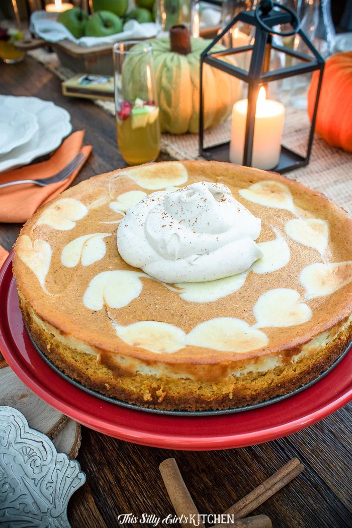 Close up of Pumpkin Cheesecake on pan topped with whipped topping