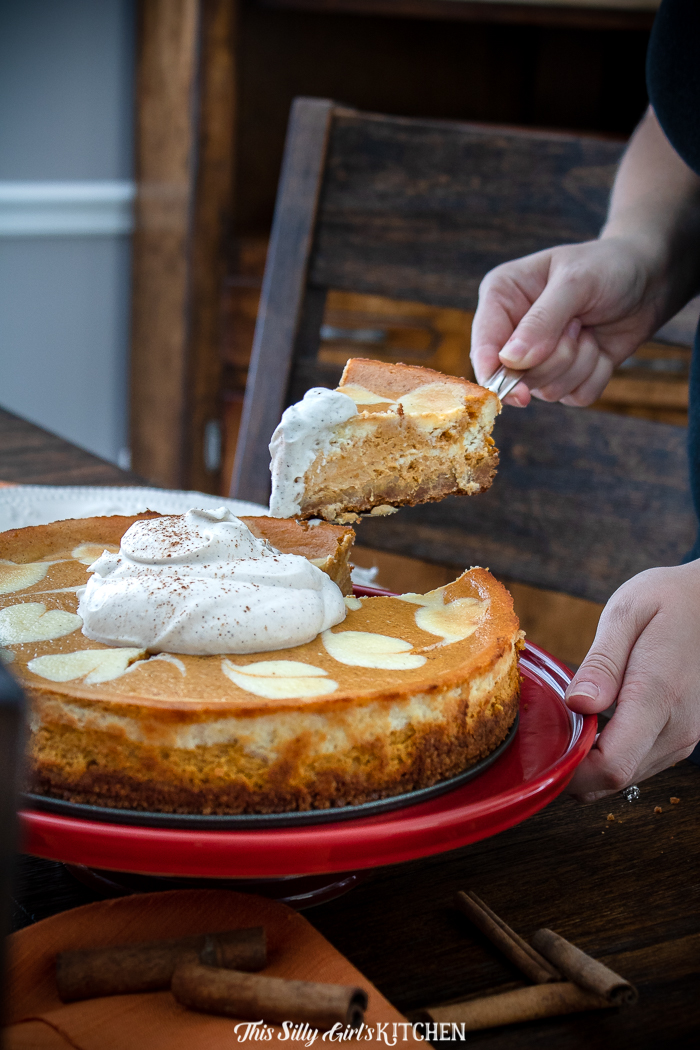 Hand pulling out a slice of cheesecake