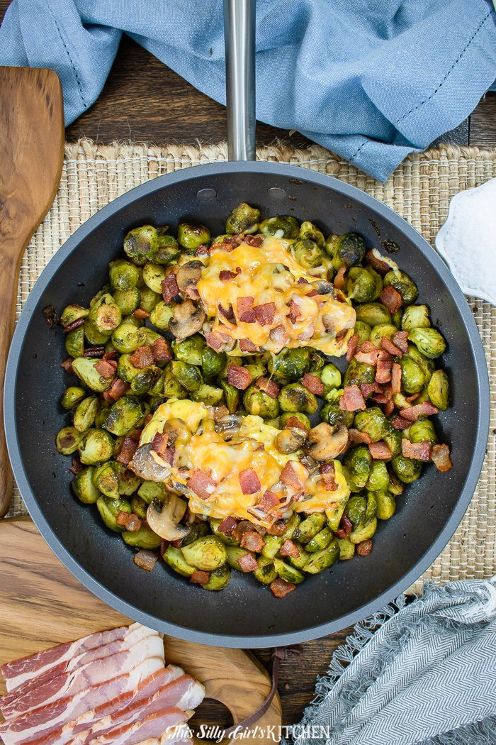 Chicken overhead in pan with melted cheese and Brussel sprouts