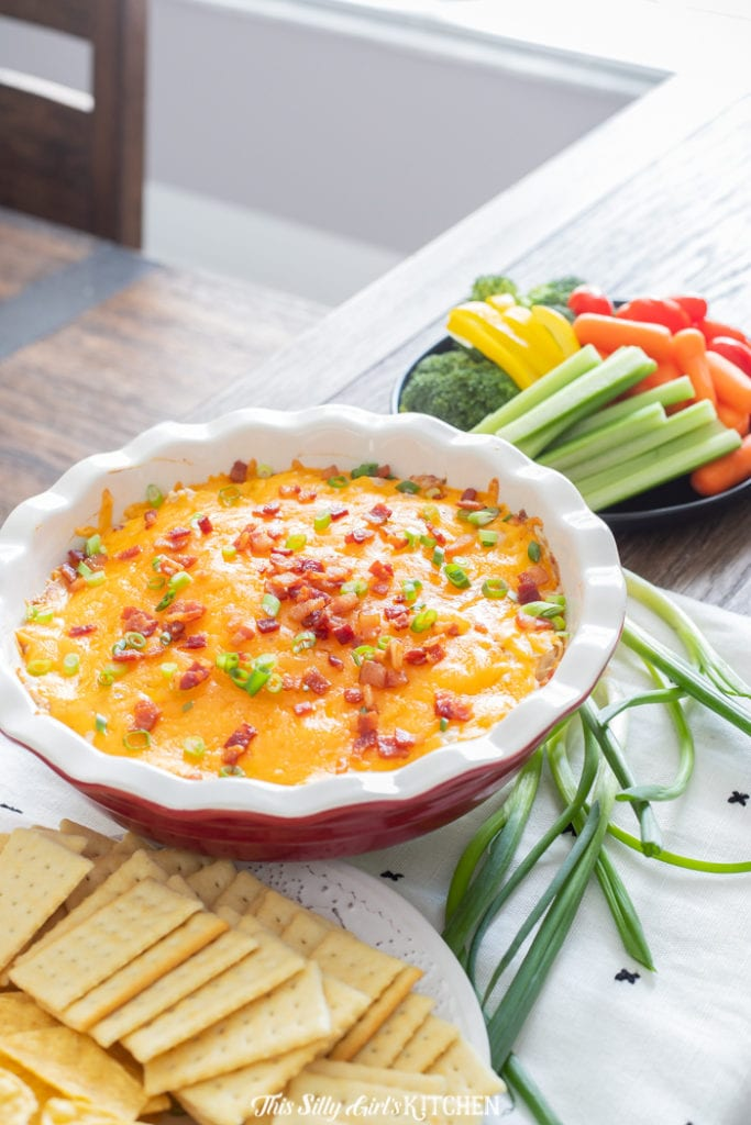 Bacon Ranch Chicken Dip in pie plate surrounded by crackers and vegetables