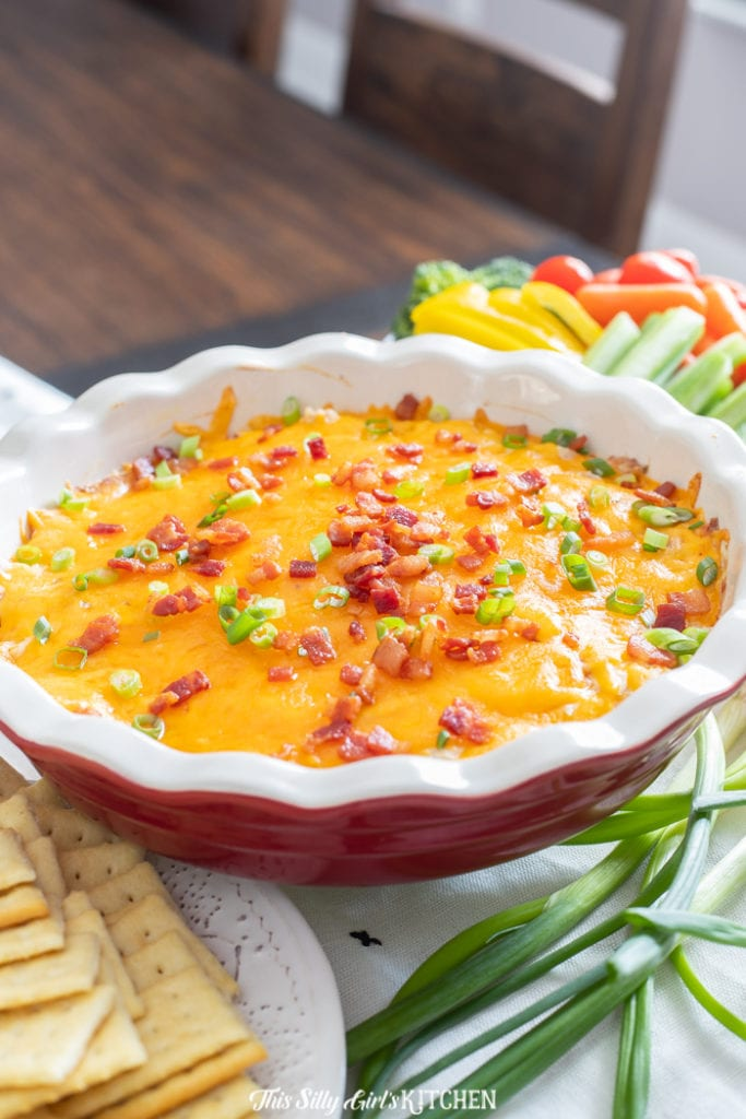 Close up of chicken dip in pie plate topped with bacon and green onions