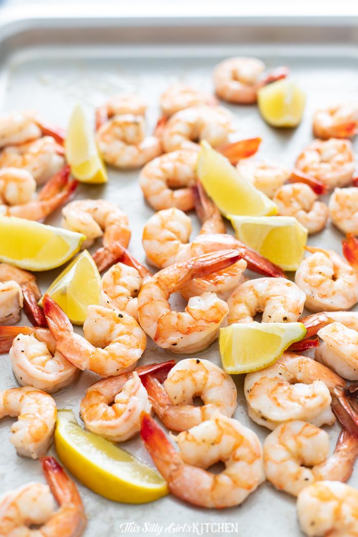 Shrimp and lemon wedges on baking pan