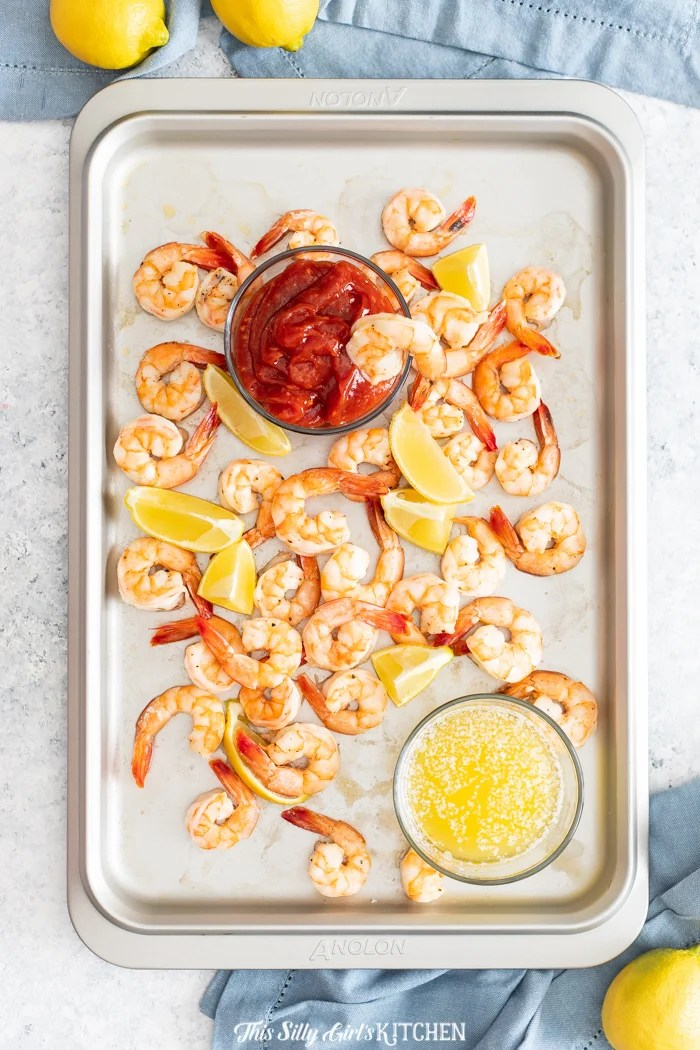 Overhead of Roasted Shrimp Cocktail with melted butter, cocktail sauce and shrimp and lemon wedges on pan