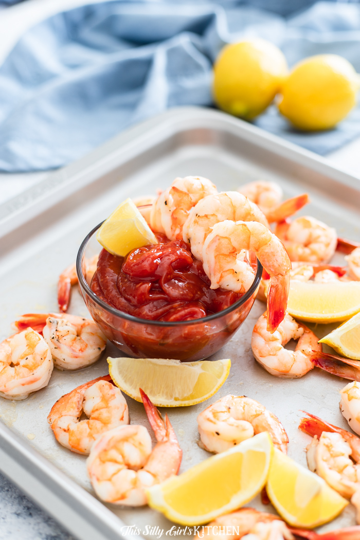 Roasted Shrimp Cocktail being served with sauce and shrimp over bowl of sauce