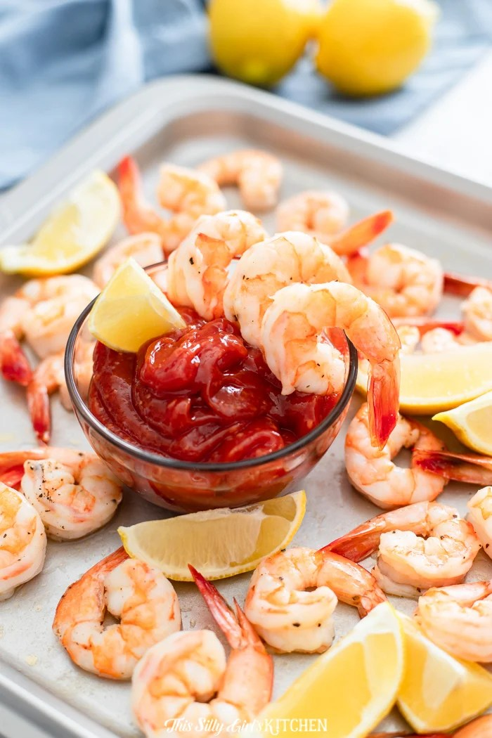 Roasted Shrimp Cocktail on sheet pan with cocktail sauce in middle