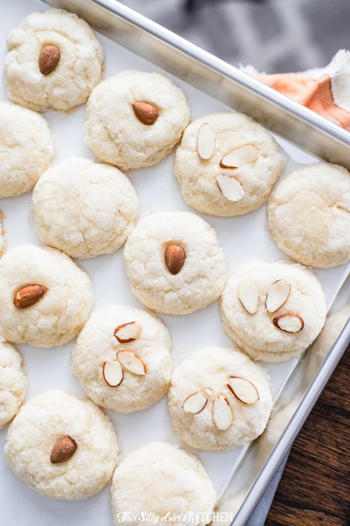 Meltaway Almond Cookies, made with an addictive cream cheese dough, rolled in sugar, and topped with an optional almond garnish! #recipe from thissillygirlskitchen.com #cookies #almondcookies #creamcheesecookies #meltawaycookies