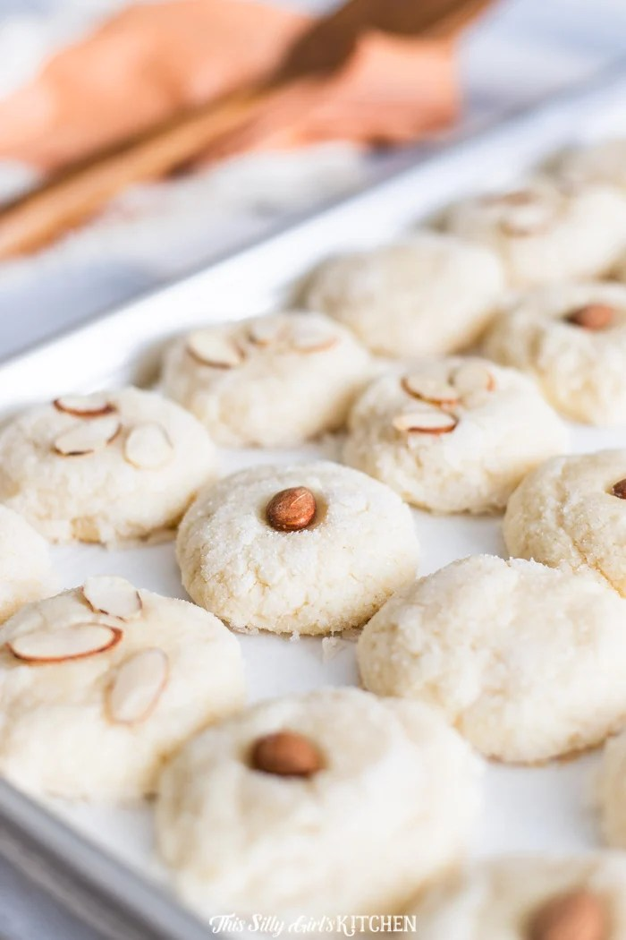 Close up of Meltaway Almond Cookies on baking sheet topped with almonds