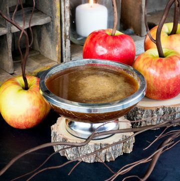 Cinnamon Buttermilk Caramel Sauce in silver bowl with apples square image.