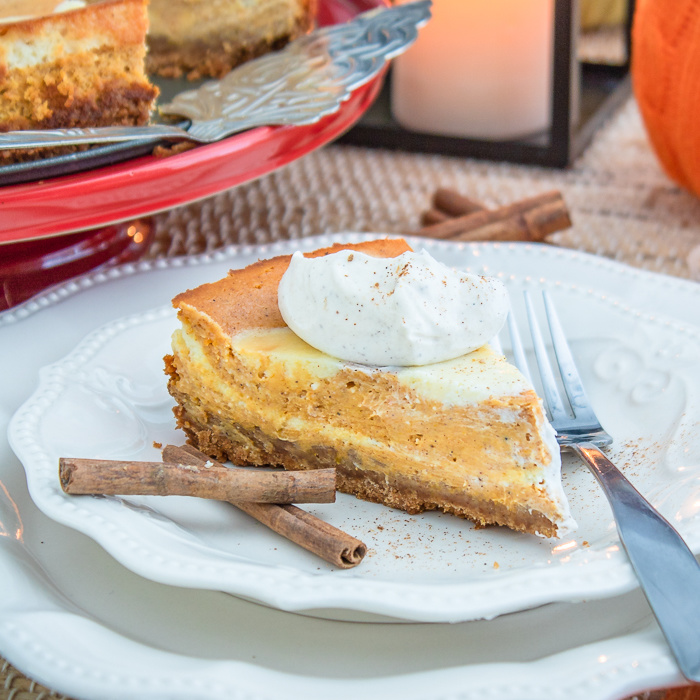 Pumpkin cheesecake on plate with cinnamon sticks square image
