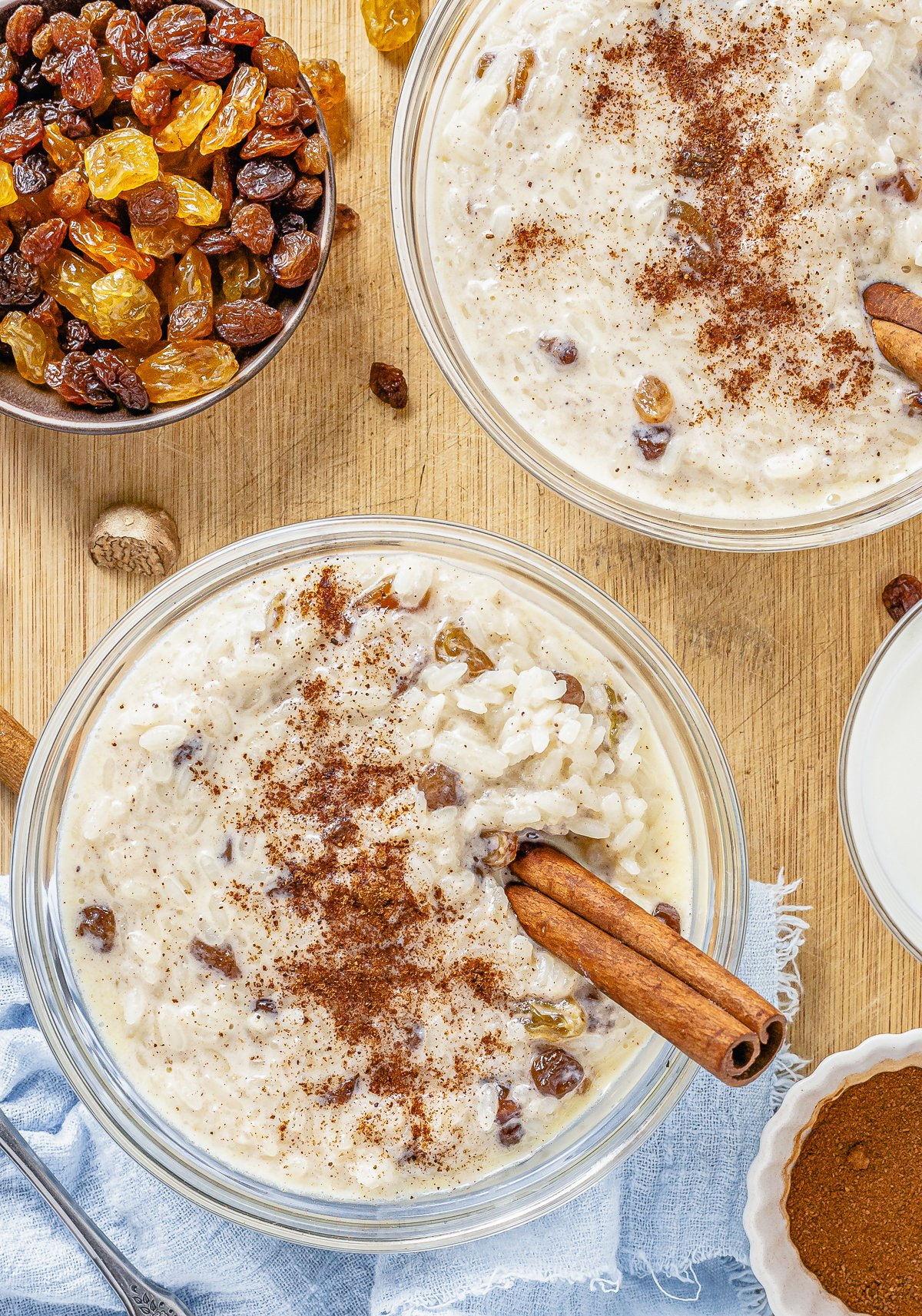 Two bowls of Rice Pudding with Cooked Rice with cinnamon and cinnamon sticks.
