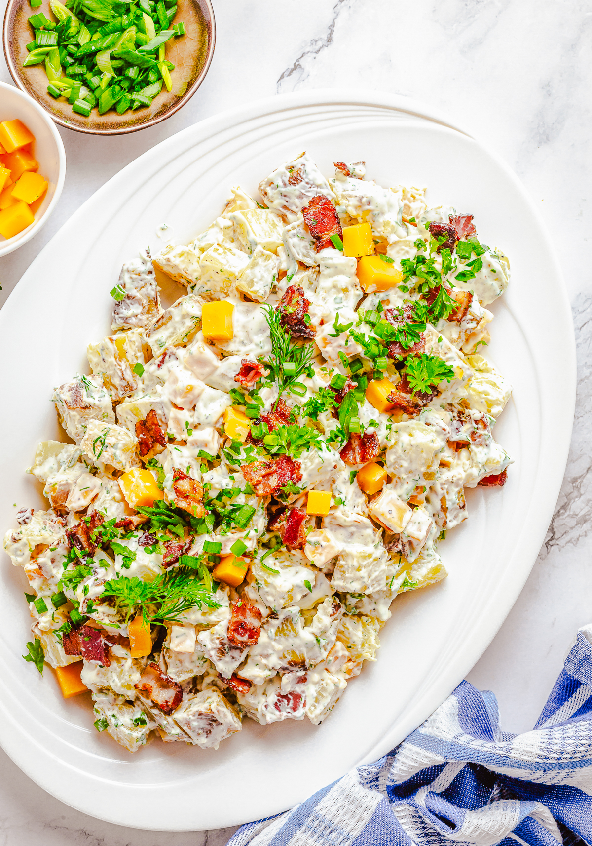 Overhead of Ranch Potato Salad recipe on platter topped with scallions