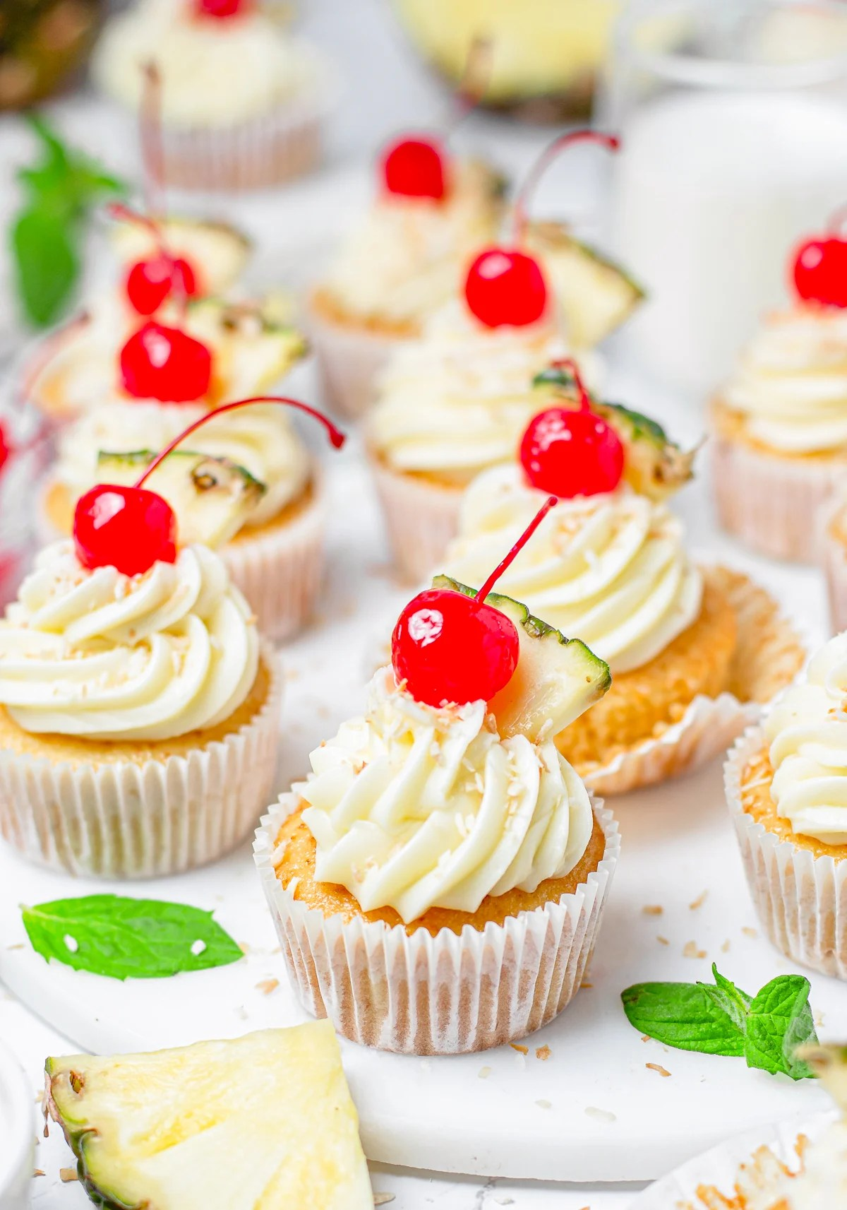 Pina Colada Cupcakes decorated topped with cherries on white platter