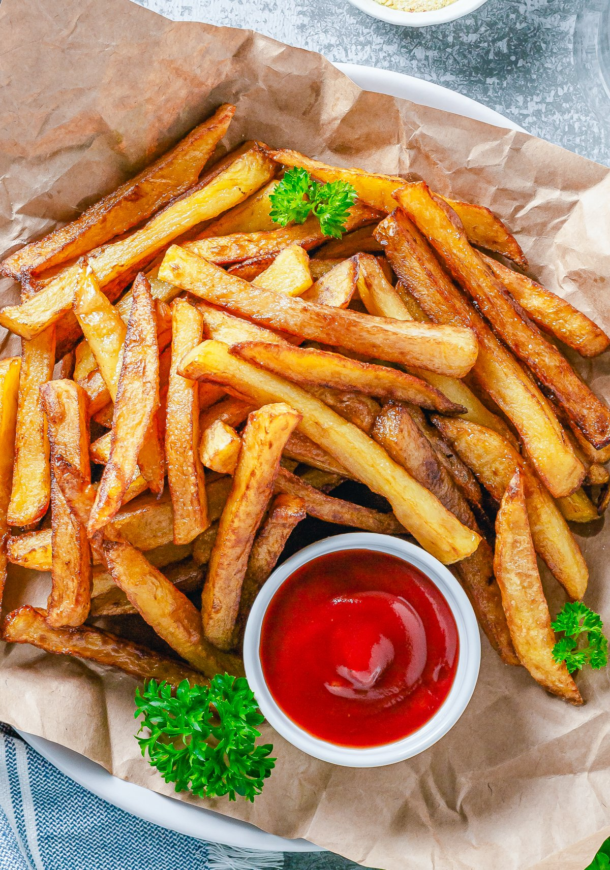Overhead photo of French Fries on parchment paper with ketchup and parsley.