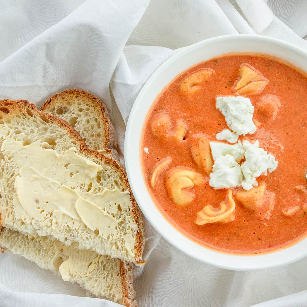 The best tomato soup in bowl with bread next to it square image