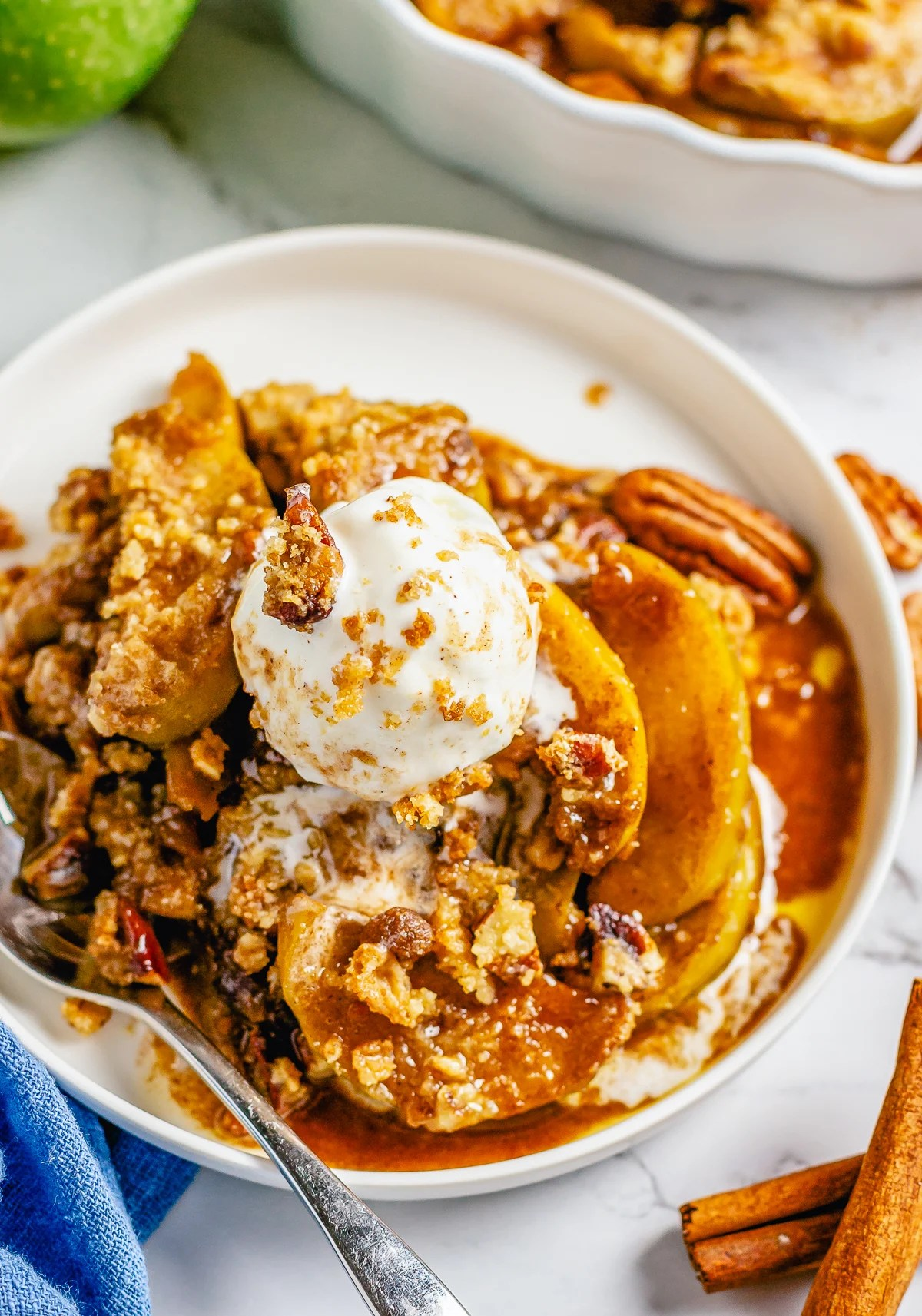 Close up of crumble on white plate topped with ice cream and more nuts with utinsel.