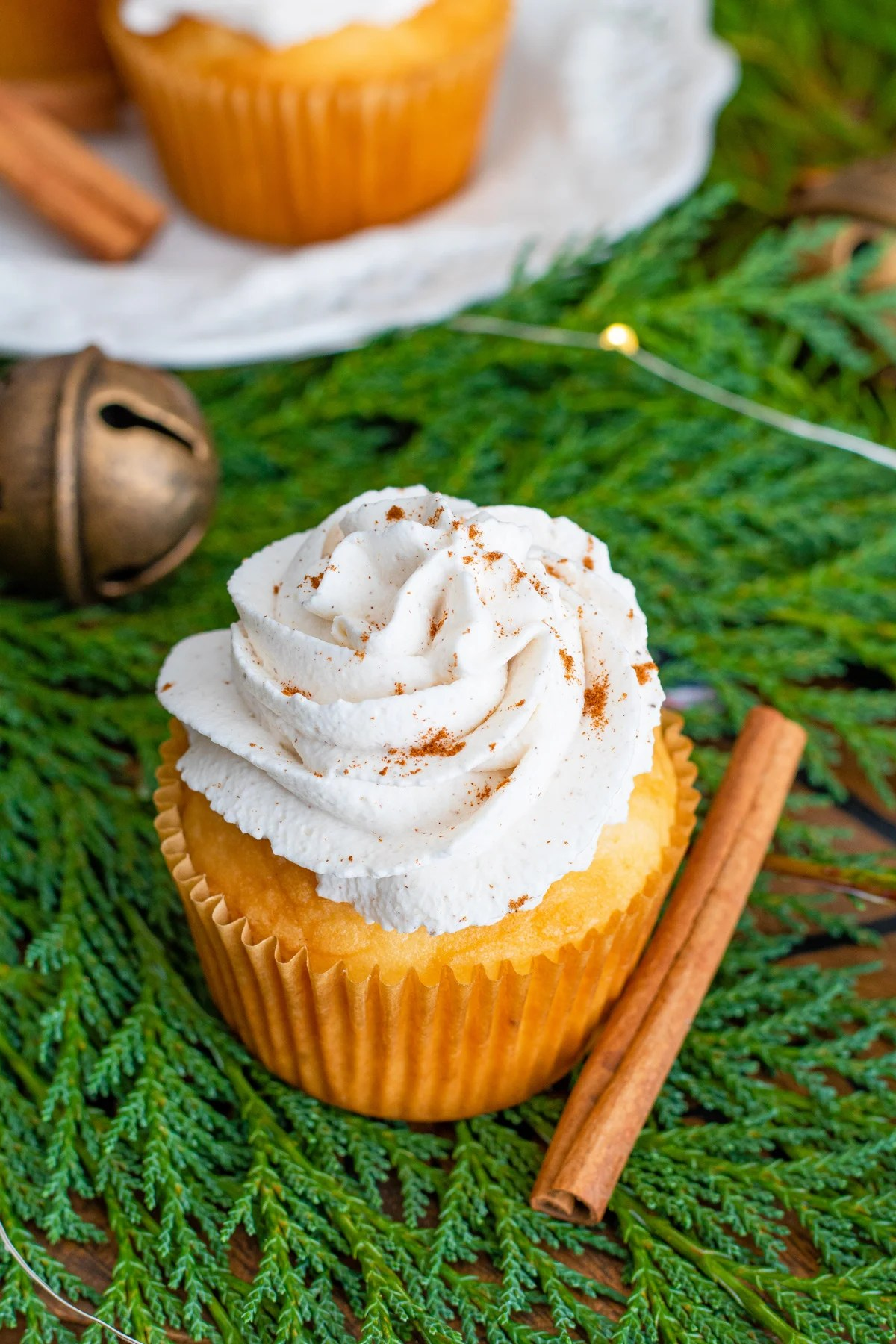 Overhead of eggnog cupcakes with cinnamon stick next to it