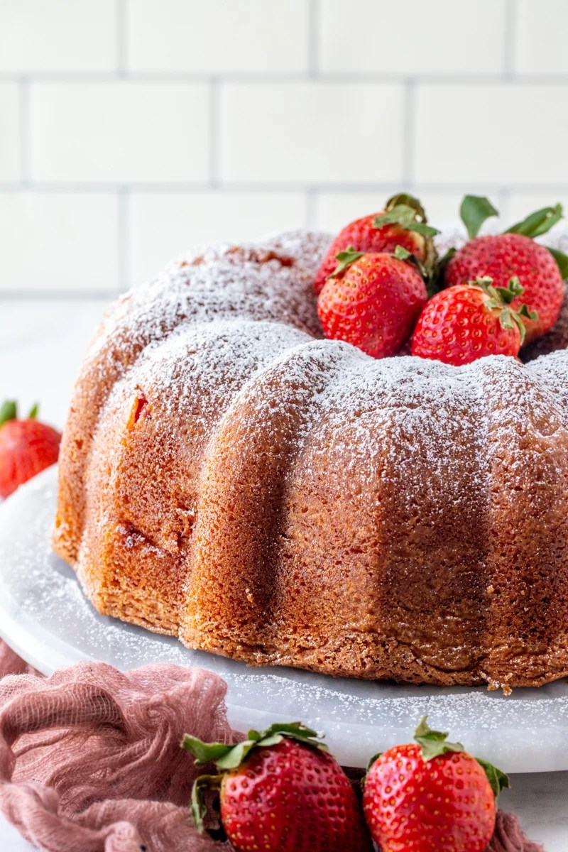 Finished Bundt Cake topped with powdered sugar and strawberries