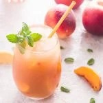 Close up of drink in glass with straw and peaches