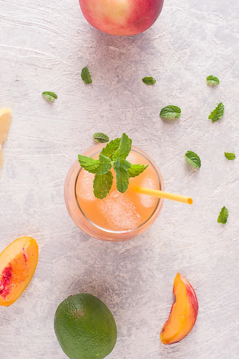 Overhead of Peach Arnold Palmer in glass with straw and mint