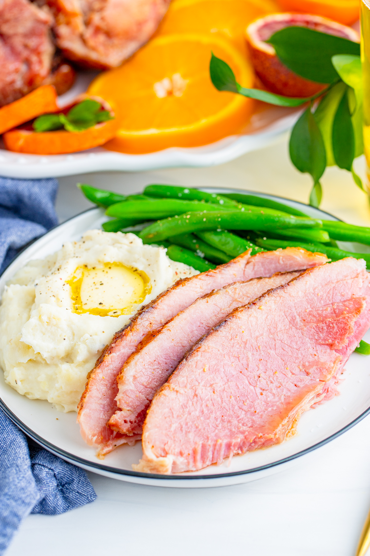 Sliced Honey Baked Ham on plate with mashed potatoes and green beans