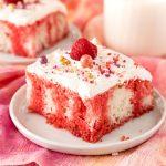 Square photo of Raspberry Jello Poke Cake decorated on white plate