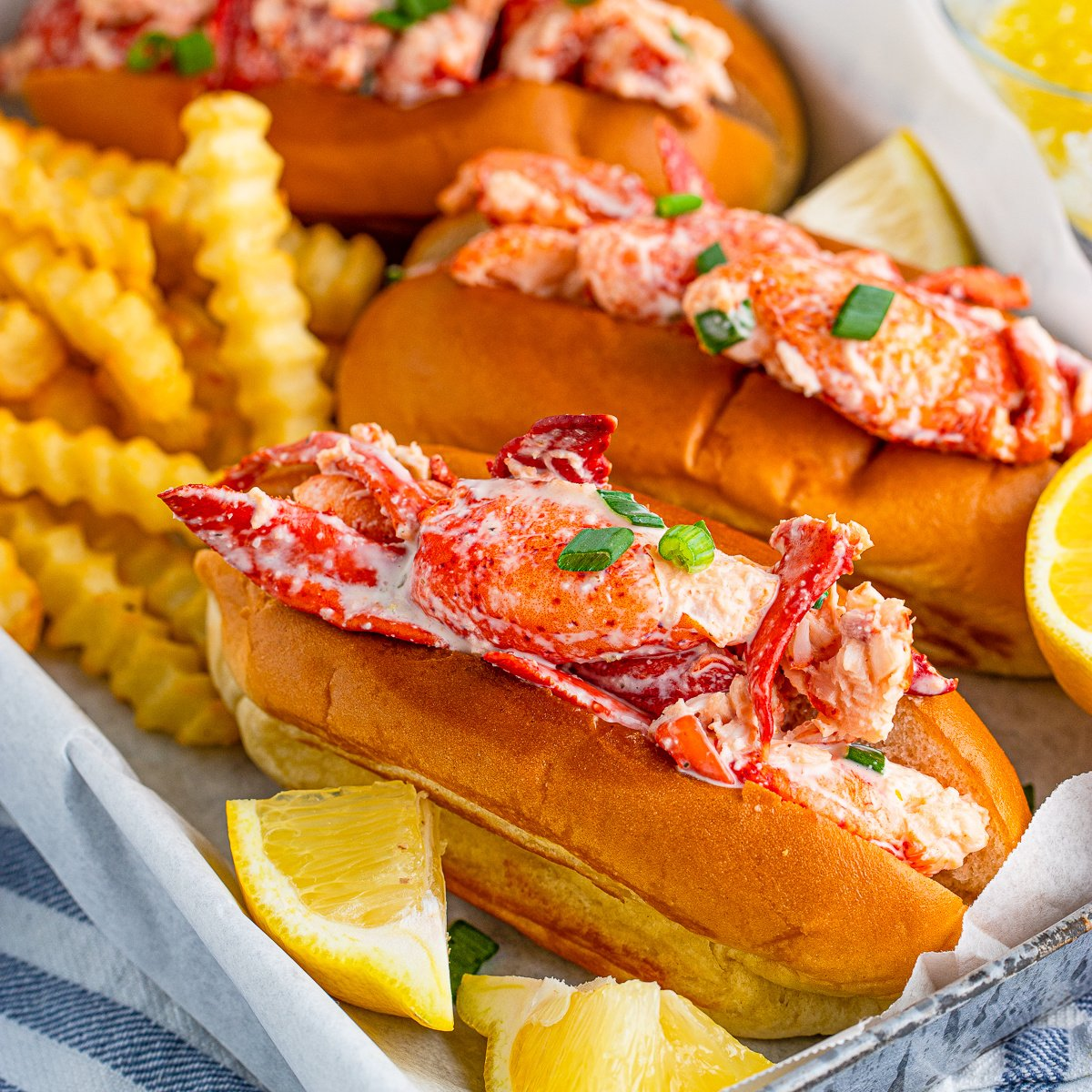 Square image of Lobster Rolls ion tray with French fries and lemon wedges