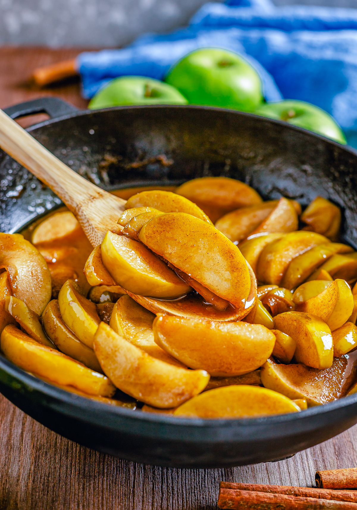Fried Apples in skillet with wooden spoon.