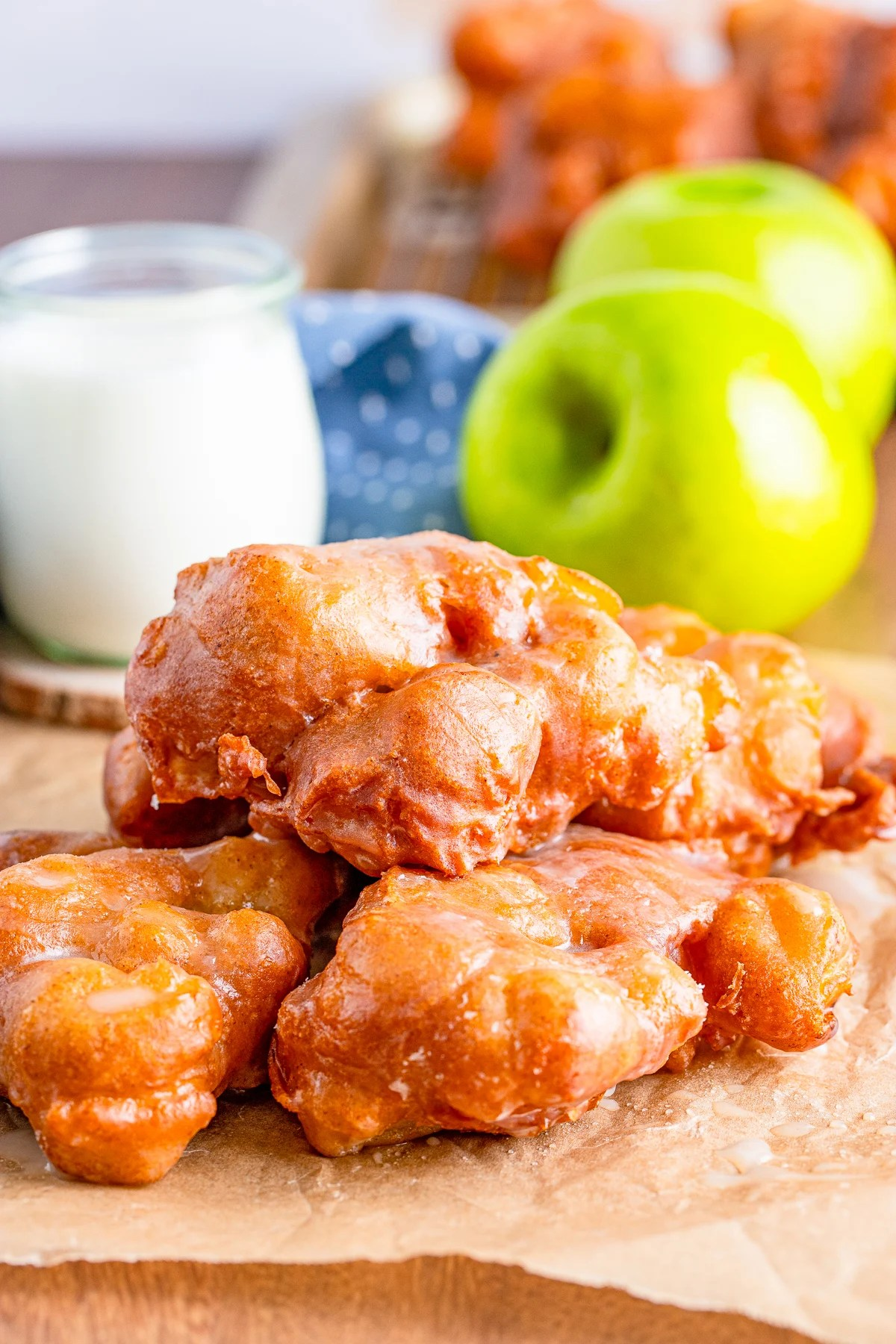 Three stacked Apple Fritter Recipe on parchment paper with apple and milk in background.