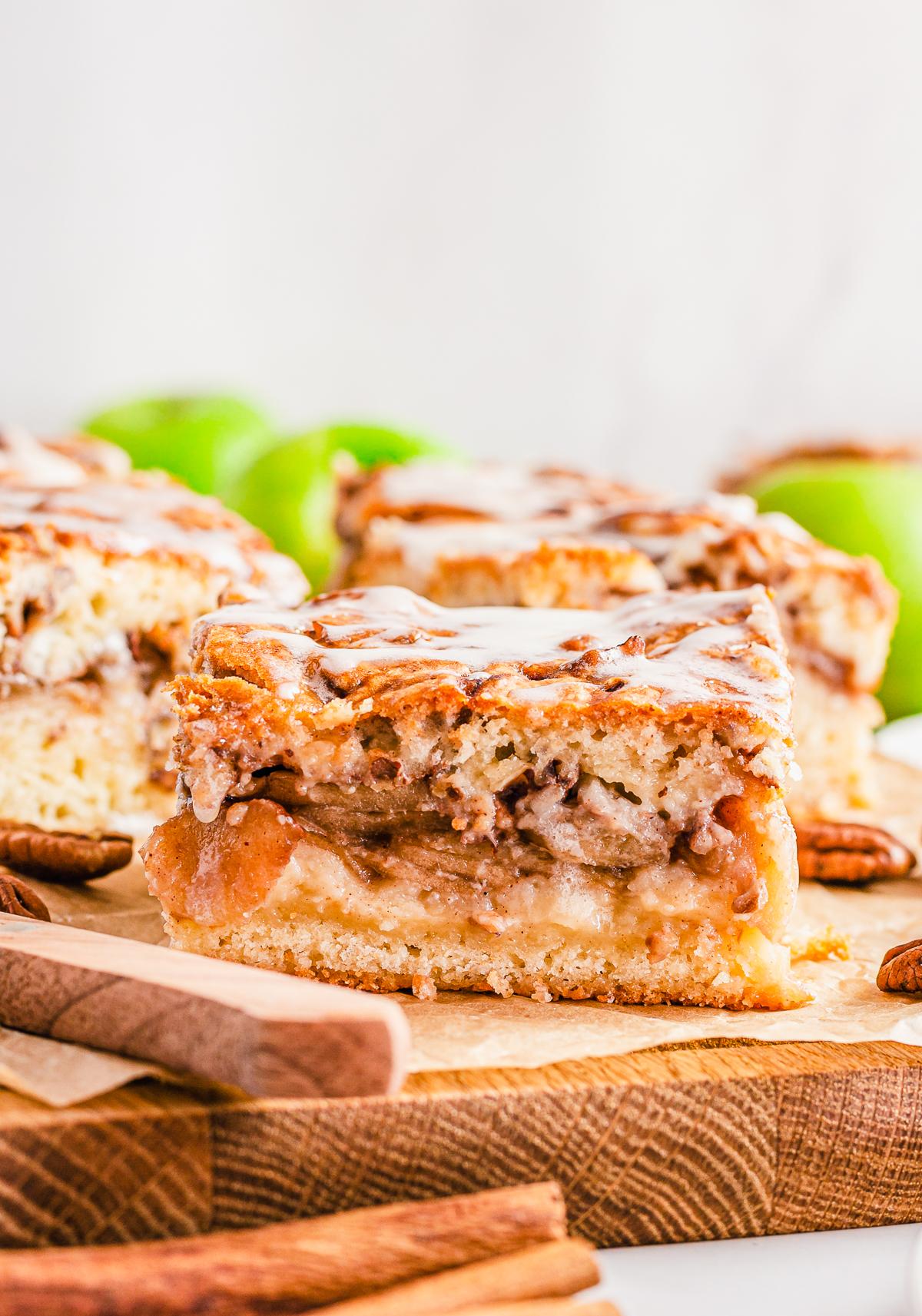 Cut Apple Pie Bars on wooden board glazed with cinnamon sticks.