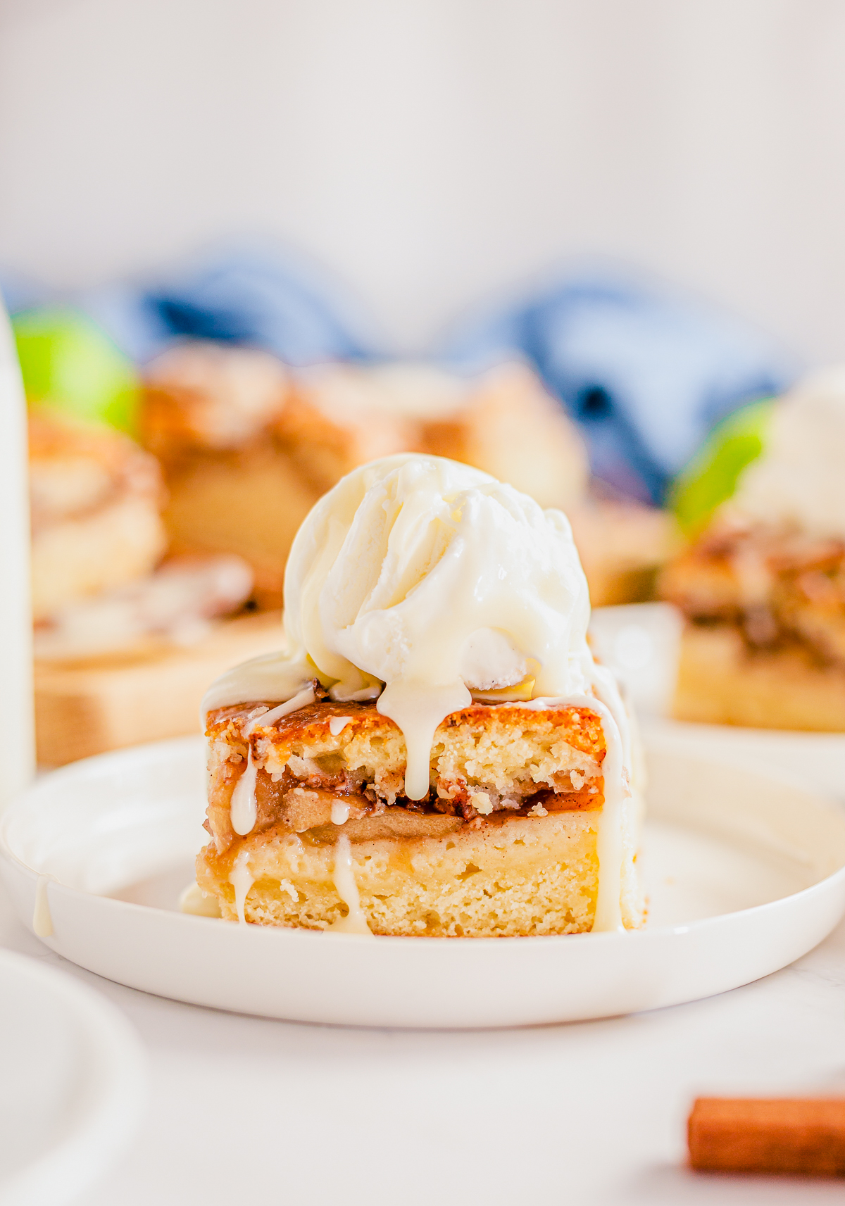 Apple Pie Bar on white plate topped with ice cream.