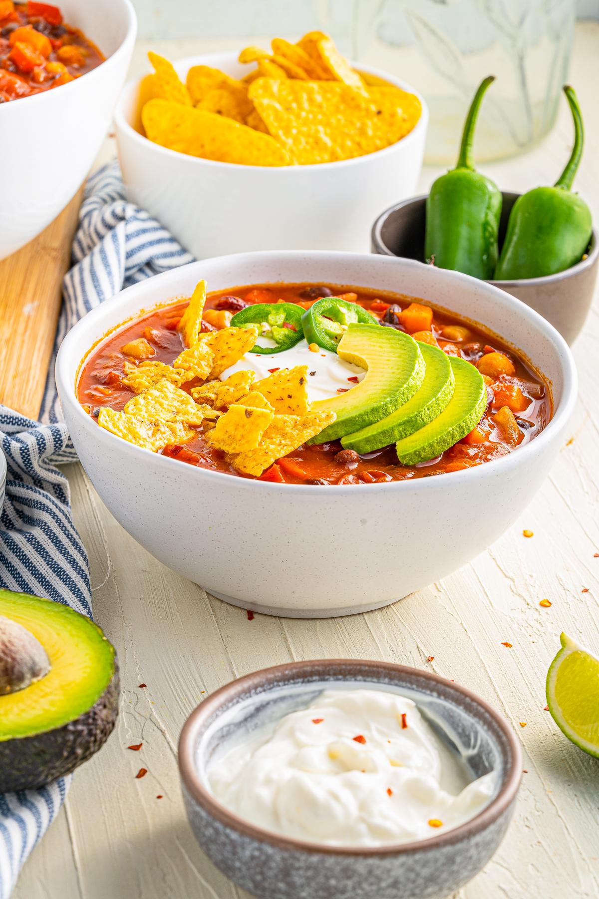 Vegetarian Chili Recipe in bowl with garnishes and garnishes around bowl.